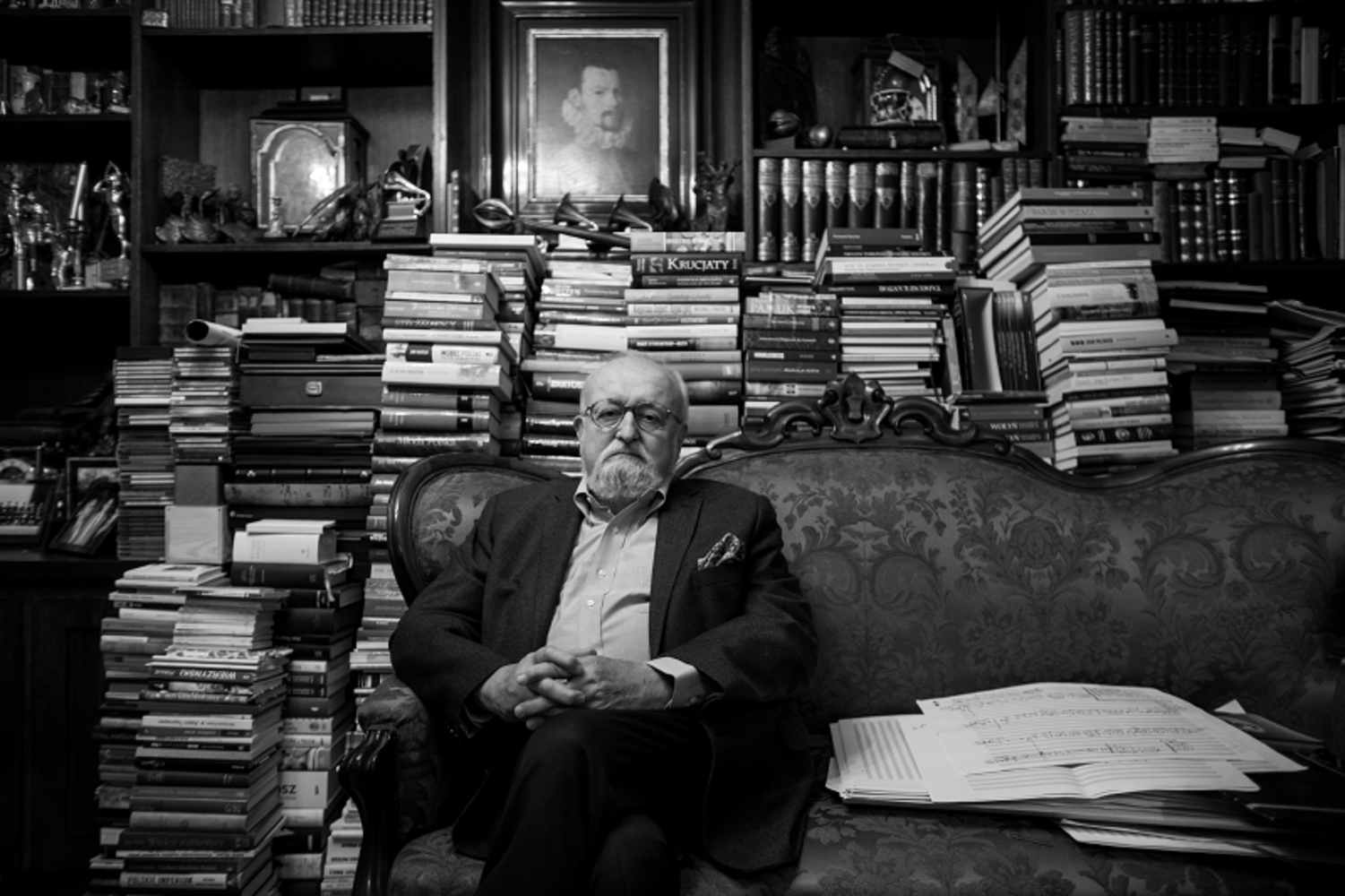 Krzysztof Penderecki sits on a settee surrounded by stacks of books