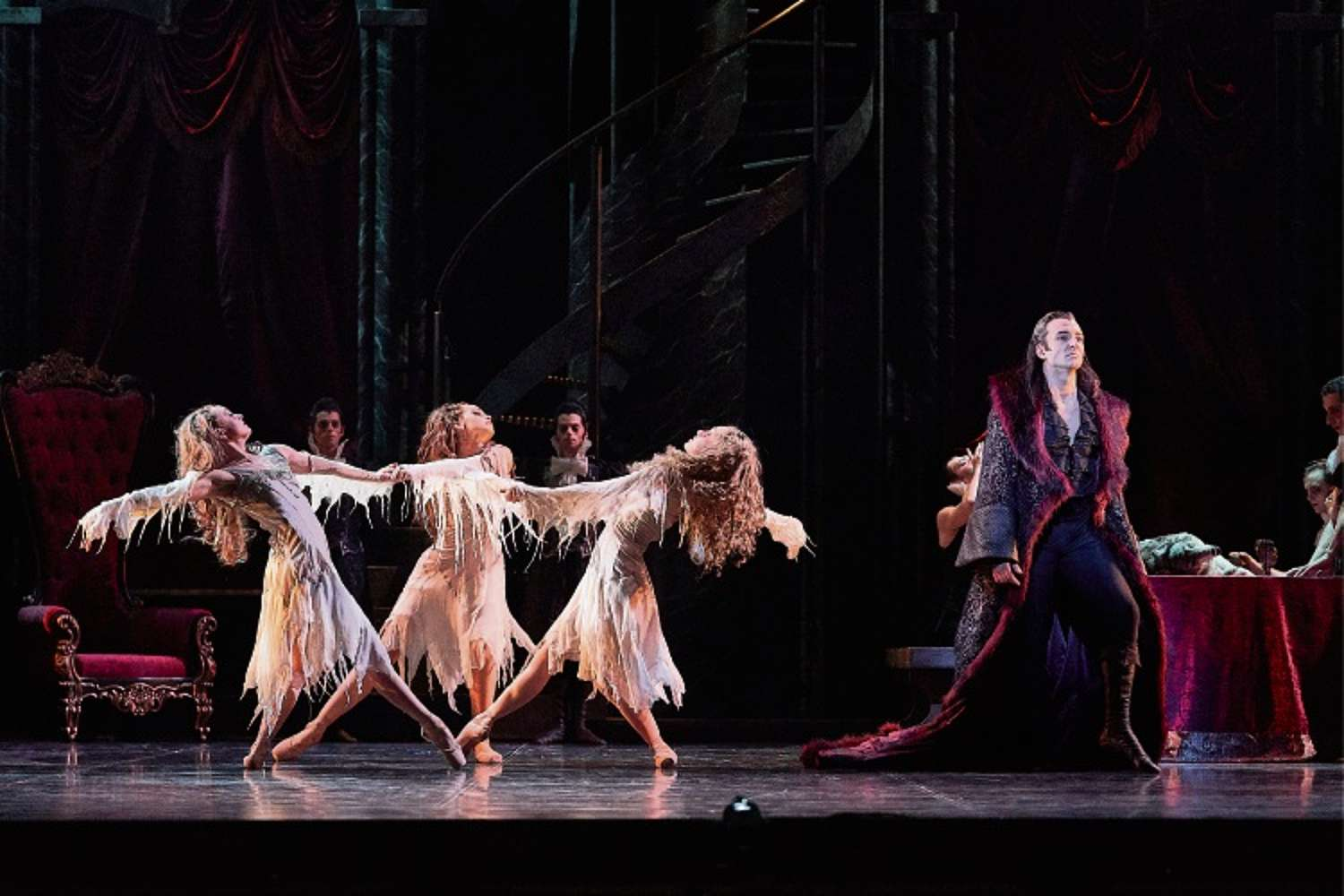 Stage shot with three female dancers on the left and male dancer as Dracula on the right