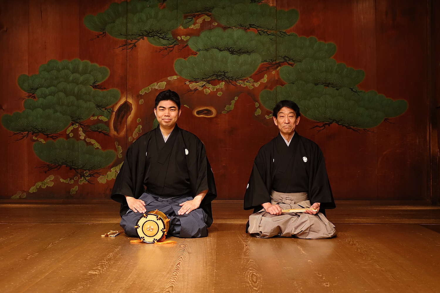 Two Japanese men kneeling onstage in kimonos against a backdrop featuring a large tree