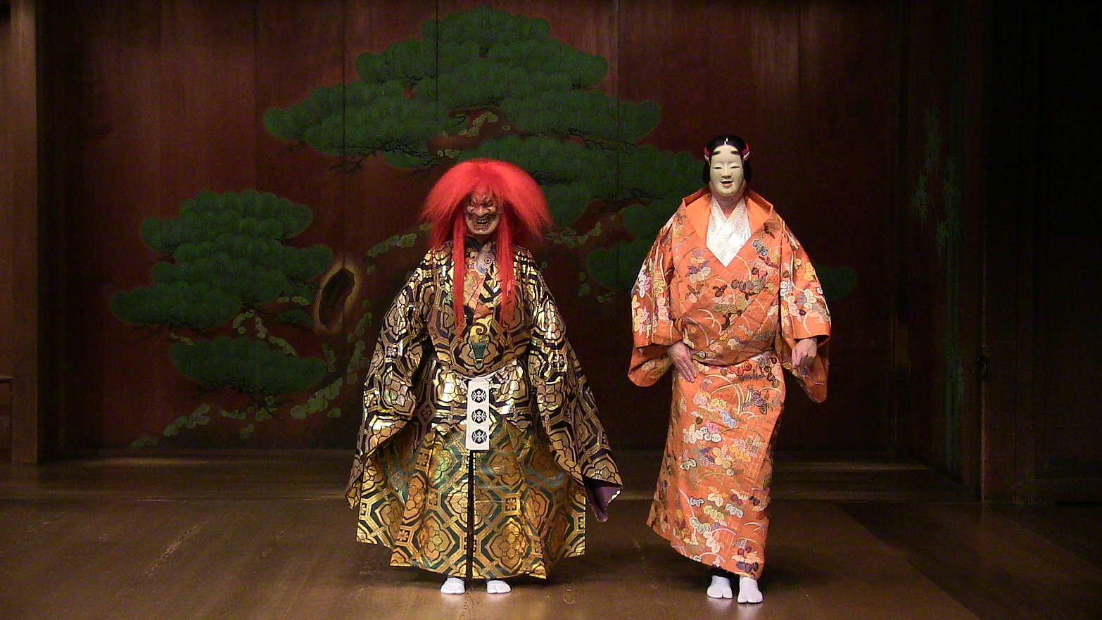 A scene from a play: In the centre of the stage two actors wearing colorful kimonos and Japanese masks