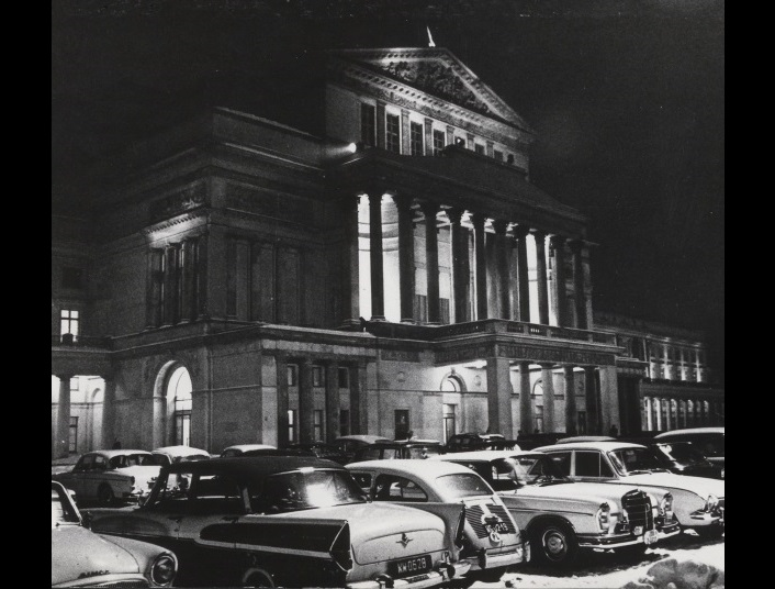 A 1960s photo of the Teatr Wielki from Teatralny Square at nightfall with cars parked in front of the main entrance