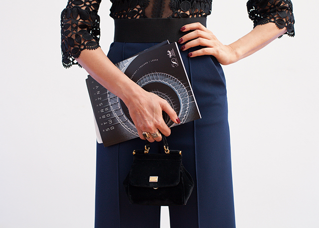 Pictured: a close-up showing a woman from the chest to the knees, wearing a black lace blouse and elegant navy-blue trousers, holding a handbag and an opera programme.
